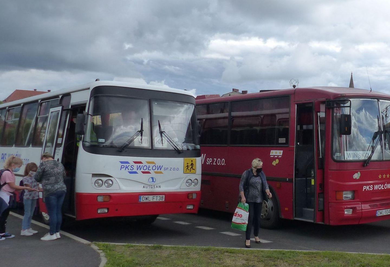 Dwa autobusy PKS Wołów na parkingu przy Szkole Podstawowej. Wchodzą do nich uczniowie.