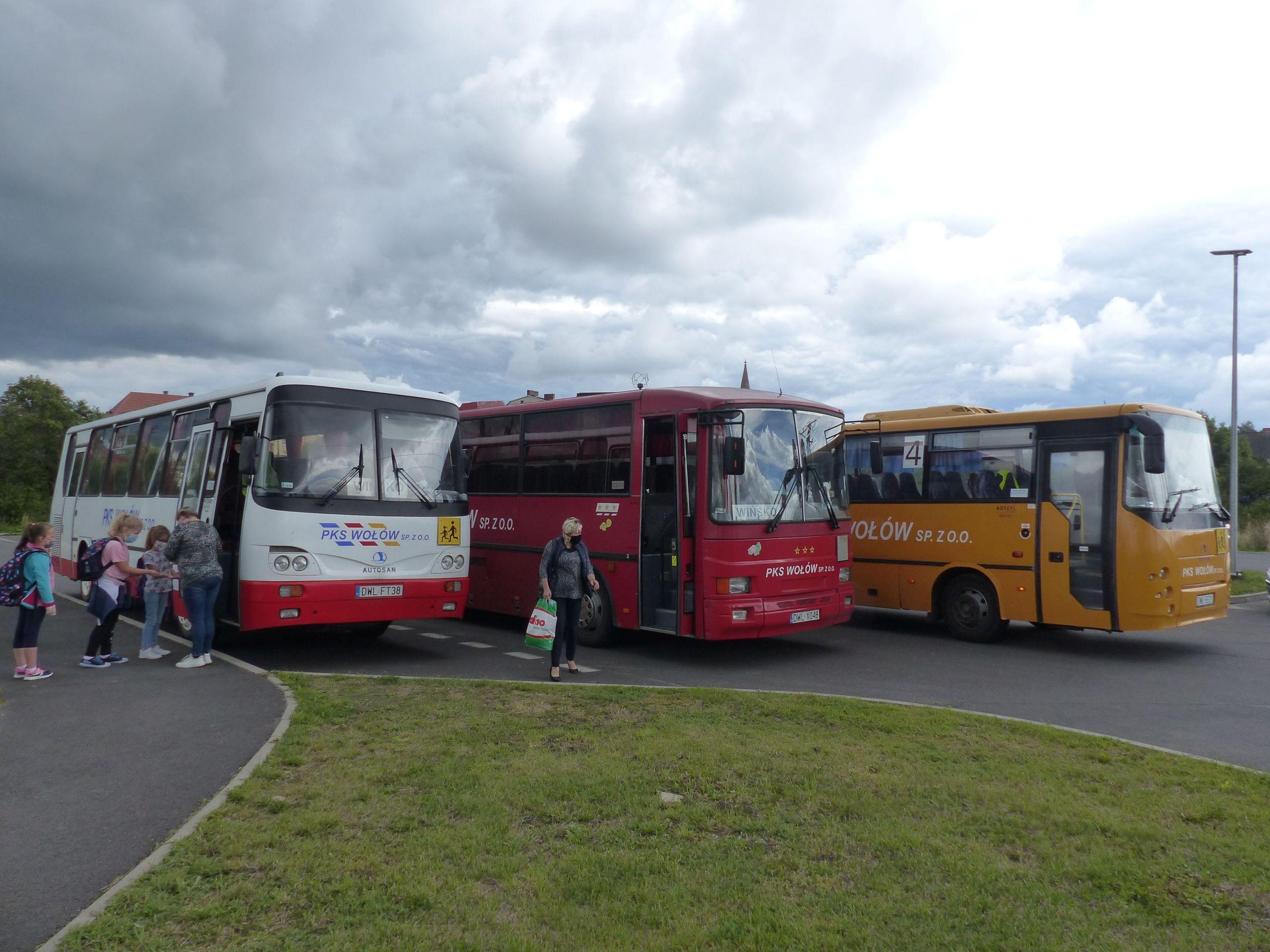 Trzy autobusy PKS Wołów na parkingu przy Szkole Podstawowej w Wińsku. Wchodzą do nich uczniowie.