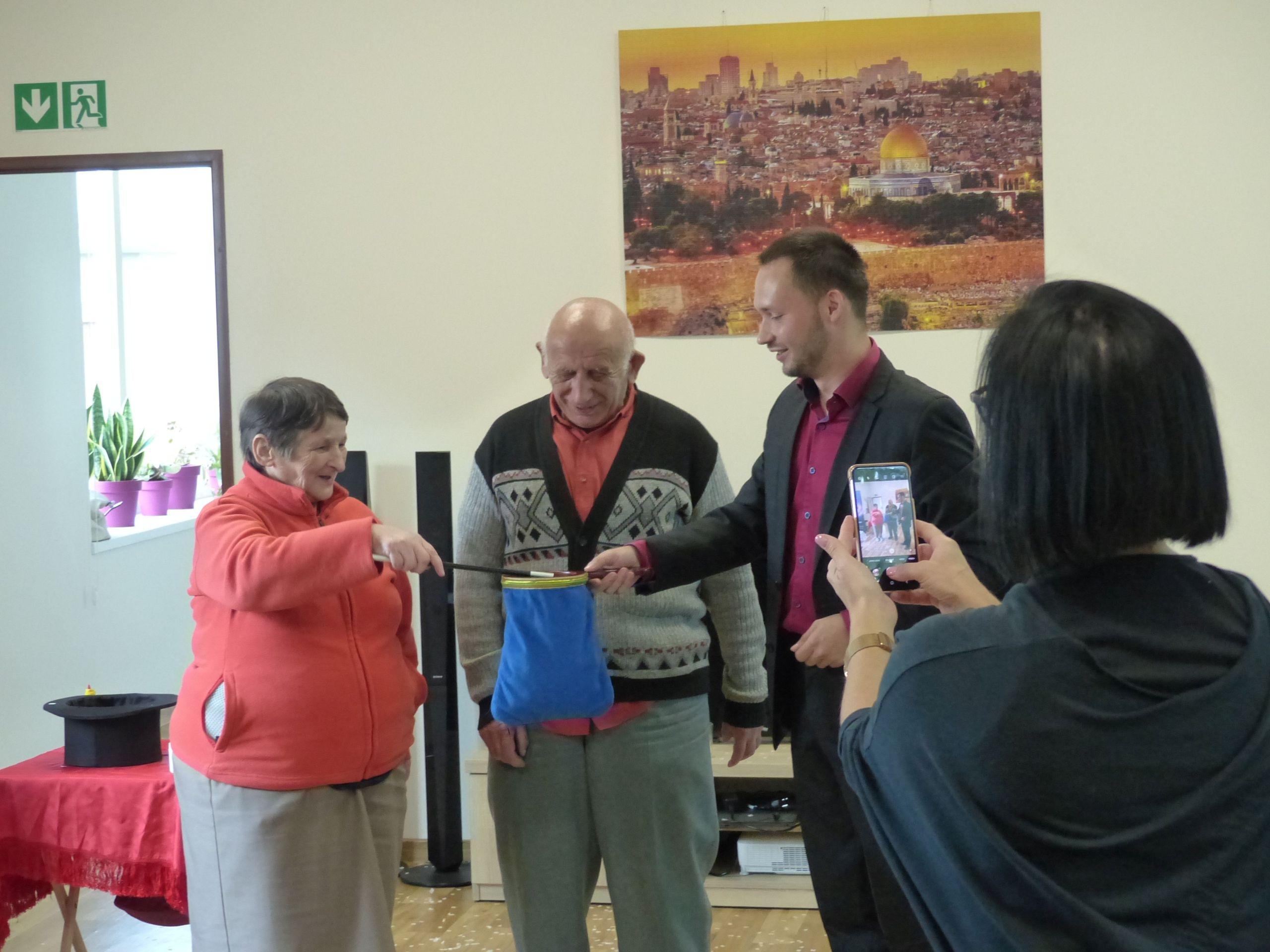 Dwoje seniorów z magikiem i opiekunka robiąca zdjecie telefonem komórkowym.
