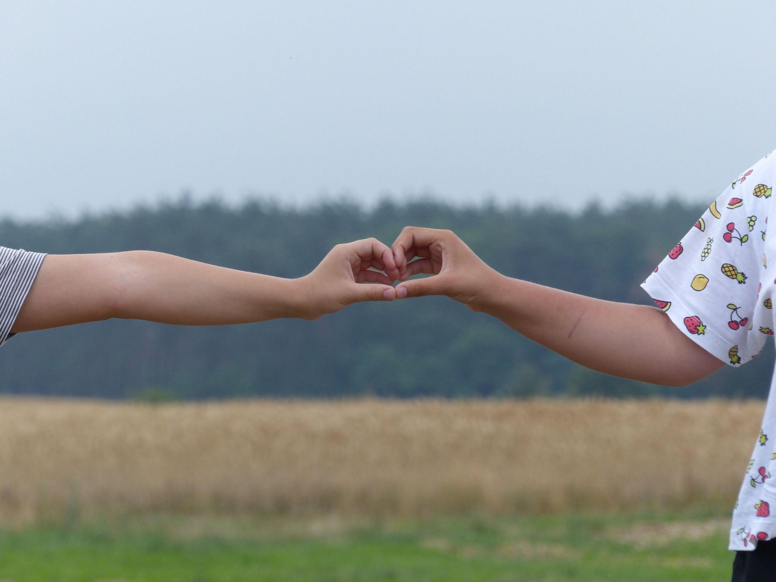 Jedna z działek na sprzedaż pokazana przez pryzmat dziecięcych rąk złożonych w kształcie serca.