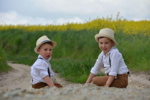 Dwoje dzieci, chłopców, na łące. Ubrani w koszule, brązowe spodnie z szelkami i kapelusze.