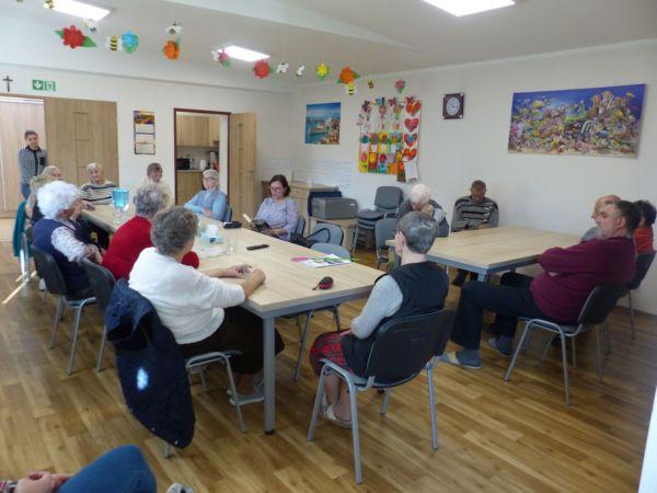Głośne czytanie u seniorów. Czyta Teresa Lewandowska, seniorzy siedzą przy stołach.