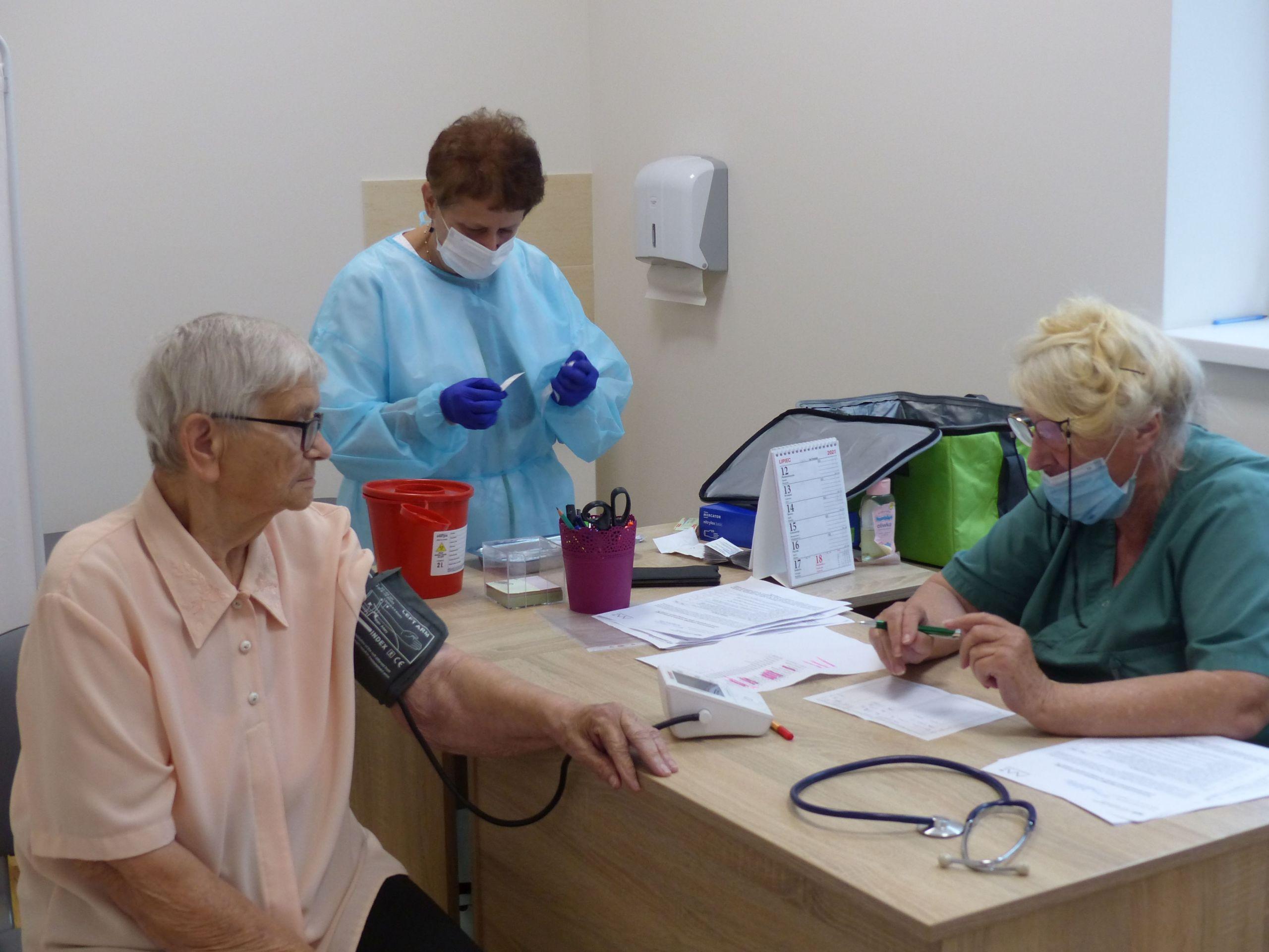 Trzy osoby. Seniorka ma mierzone ciśnienie, pielęgniarka przygotowuje szczepionkę.