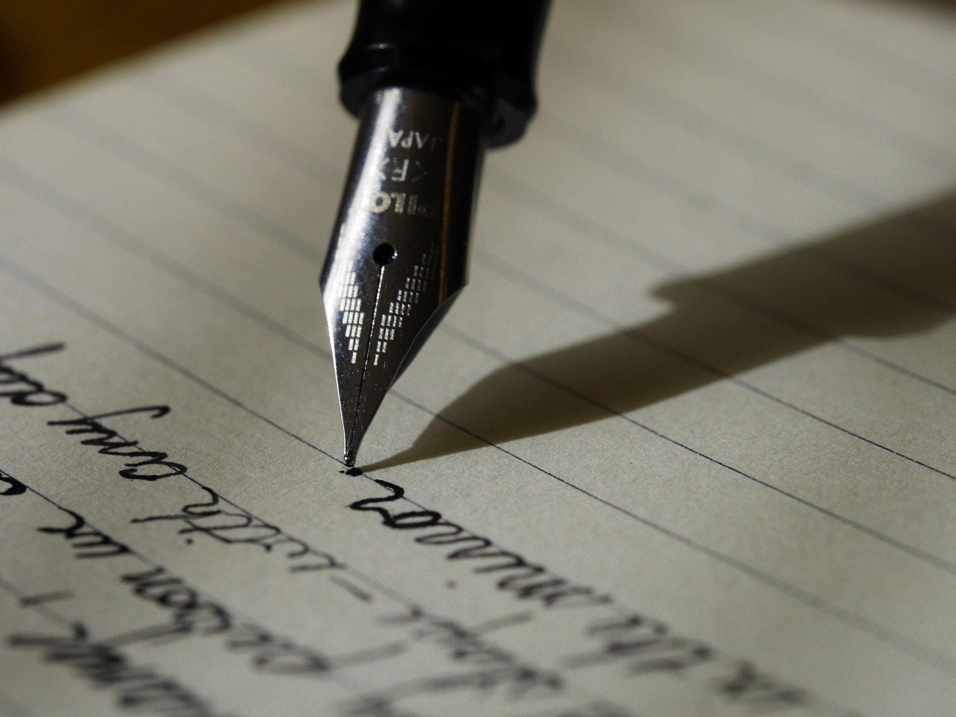 Pisanie piórem po kartce papieru.
